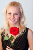 Portrait of an attractive woman with a rose with focus on woman — Stock Photo
