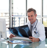Good-looking male doctor examining a x-ray — Stock Photo