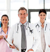 Senior Smiling doctor with his colleagues — Stock Photo
