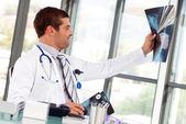 Hispanic doctor examining a x-ray — Stock Photo
