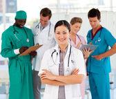 Atrakcyjna kobieta lekarz z zespołem — Zdjęcie stockowe