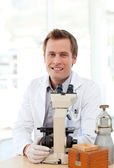 Male scientist looking through a microscope — Stock Photo