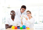 Group of scientists examining test-tubes — Stock Photo