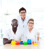 Smiling scientists examining test-tubes — Stock Photo