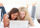 Friend girls shopping online in a bedroom — Stock Photo