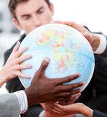 Primer plano de un equipo de negocios sostiene un globo terrestre — Foto de Stock