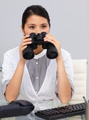 Serious young Businesswoman using binoculars — Stock Photo