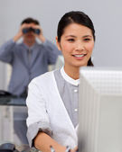 Self-assured asian businesswoman at a computer — Stock Photo
