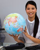 Assertive businesswoman holding terrestrial globe — Stock Photo