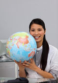 Confident asian businesswoman holding terrestrial globe — Stock Photo