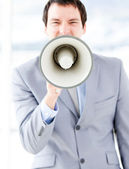 Portrait of an nervous businessman using a megaphone — Stockfoto