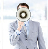 Portrait of an young businessman using a megaphone — Stock Photo