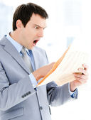 Portrait of a surprised businessman reading a newspaper — Stock Photo