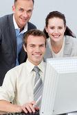 Lachende bedrijf werken samen met een computer — Stockfoto