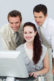 Three young business using a computer — Stock Photo