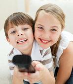 Mignon frérot et sœurette, regarder la télévision — Photo