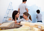 Smiling family decorating their new home — Stock Photo