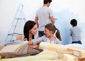Uśmiechnięta rodzina dekorowanie ich nowego domu — Zdjęcie stockowe