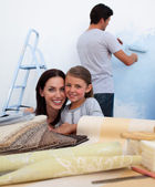 Smiling family renovating their new home — Stock Photo