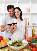 Smiling couple toasting and cooking — Stock Photo