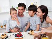 Smiling family eating pancakes for breakfast — Stock Photo