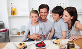 Young family eating fruits and pancakes for breakfast — Stock Photo