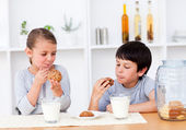 Smiling Siblings eating cookies — Stock Photo