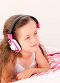 Smiling little girl listening music lying on her bed — Stock Photo