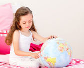 Adorable little girl holding a terrestrial globe sitting on her — Stock Photo