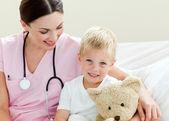 Улыбаясь доктор с ее маленькому пациенту — Стоковое фото