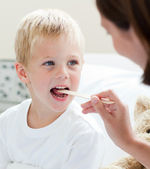 A doctor examining a child's throat — Stockfoto