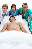 Emergency scene: medical team carriyng a patient — Stock Photo
