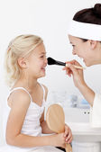 Daughter and mother putting makeup — Stockfoto