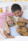 Daughter and father playing doctors with a teddy bear — Stock Photo
