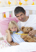 Sick girl playing with a stethoscope with her father — Foto de Stock