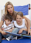 Mother reading a book with her children — Stock Photo