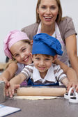 Mother and children baking in the kitchen — Stock Photo