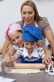 Mother and children baking cookies in the kitchen — Stock Photo