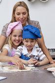 Mother helping her children baking — Stock Photo