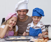 Happy father and children baking cookies together — 图库照片