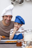 Father and son eating home-made cookies — Stock Photo