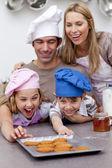 Los niños y padres comiendo galletas después de hornear — Foto de Stock