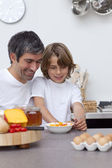 Smiling father and son having breakfast together — Stock Photo