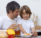 Portrait of father and son having breakfast together — Stock Photo