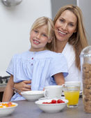 Smiling mother and daughter having breakfast together — Stock Photo