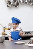 Niño con sombrero azul y delantal de la hornada — Foto de Stock