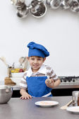 Little boy with blue hat and apron baking — Stock Photo
