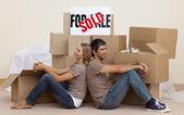 Feliz pareja sentada en el piso tras la compra de casa — Foto de Stock