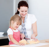 一个微笑的母亲和他的女儿准备一餐饭的肖像 — 图库照片
