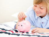 Cute boy putting a coin in a piggybank — Stock Photo